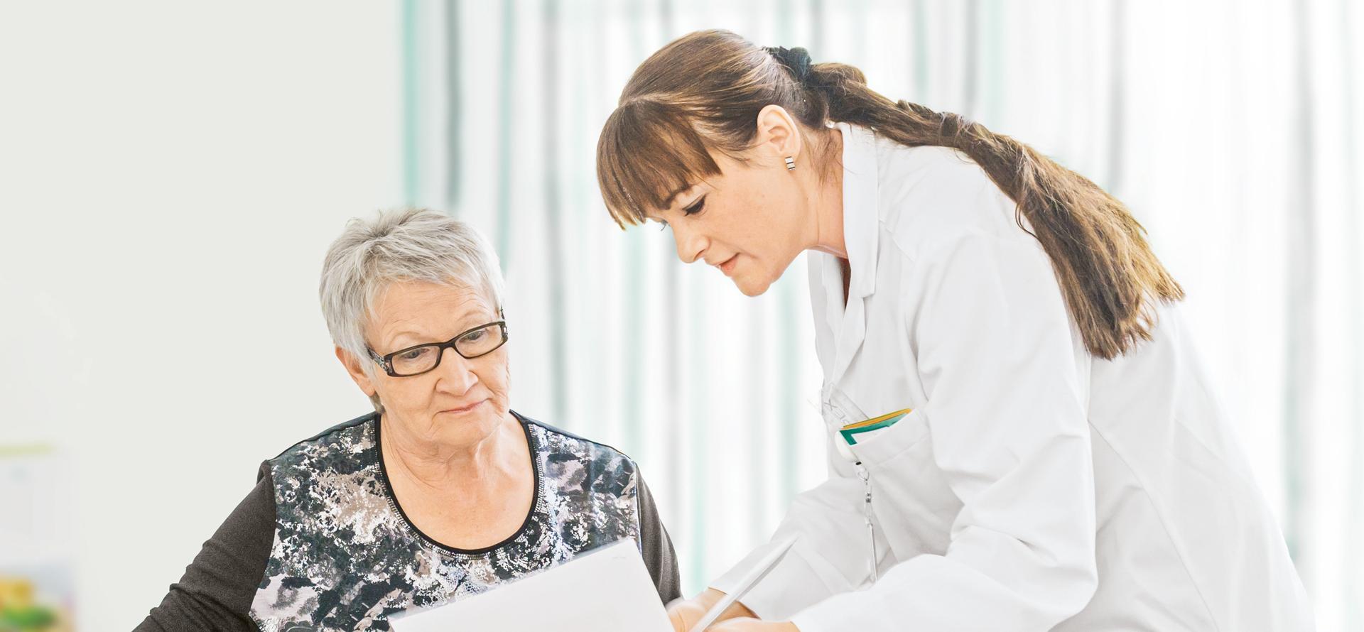 Ärztin erklärt Patientin Unterlagen