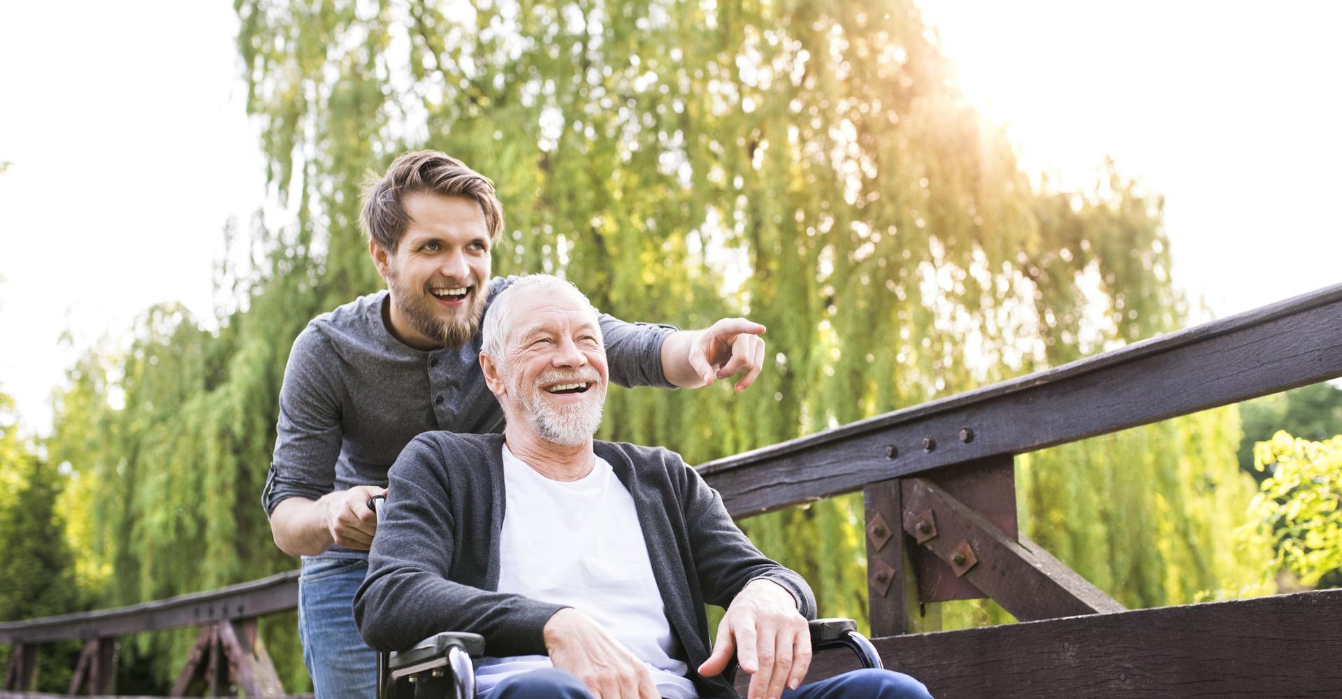 Junger Mann schiebt Rolltstuhl mit altem Mannn