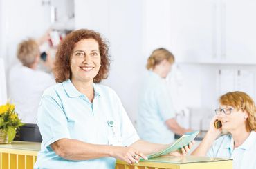 Mitarbeiterin steht am Empfang der Tagesklinik