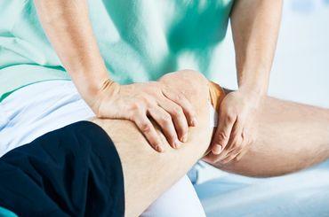 Physiotherapeutin behandelt Knie eines Patienten