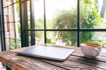 Kaffee und Laptop stehen auf dem Tisch vor dem Fenster