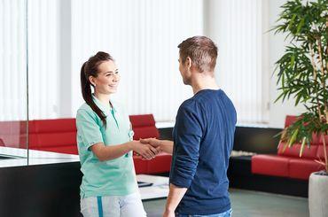 Mitarbeiterin begruesst einen Patienten
