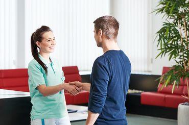 Mitarbeiterin begrüsst einen Patienten