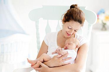 Mutter hat ihr neugebroenes Baby im Arm