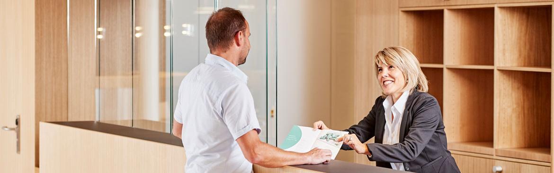 Mitarbeiterin Empfang begrüsst Patient