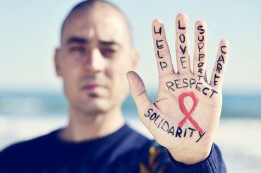 Mann hält Hand mit roter Schleife in die Luft