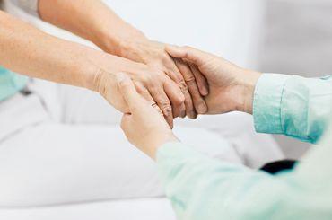 Patientin hält die Hände einer Betreuungsperson