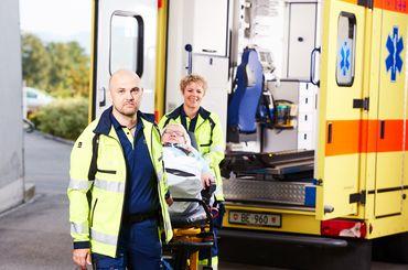 Rettungsdienstmitarbeitende mit Patientin auf Tragestuhl
