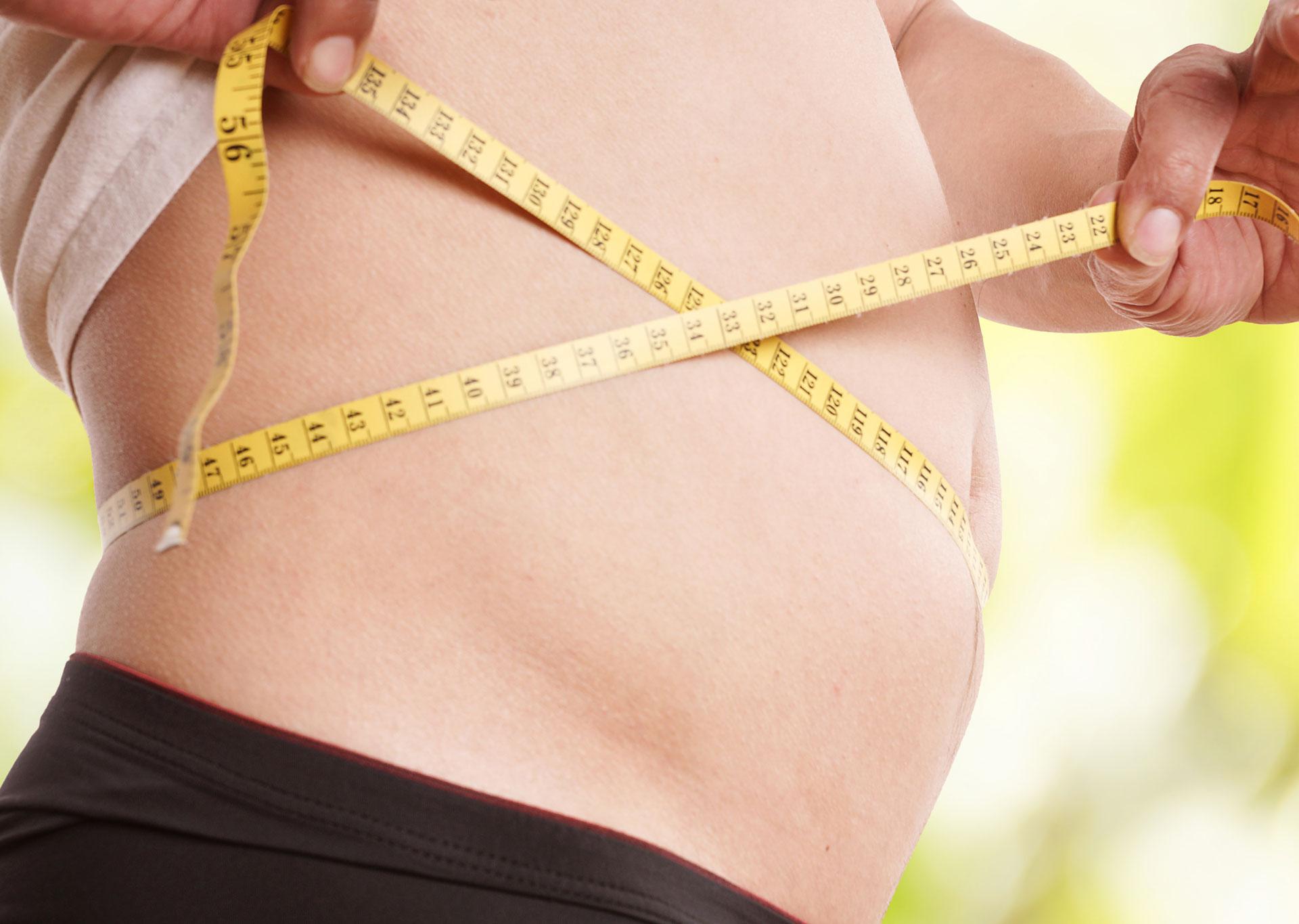 Person hält Meter um ihren Bauch
