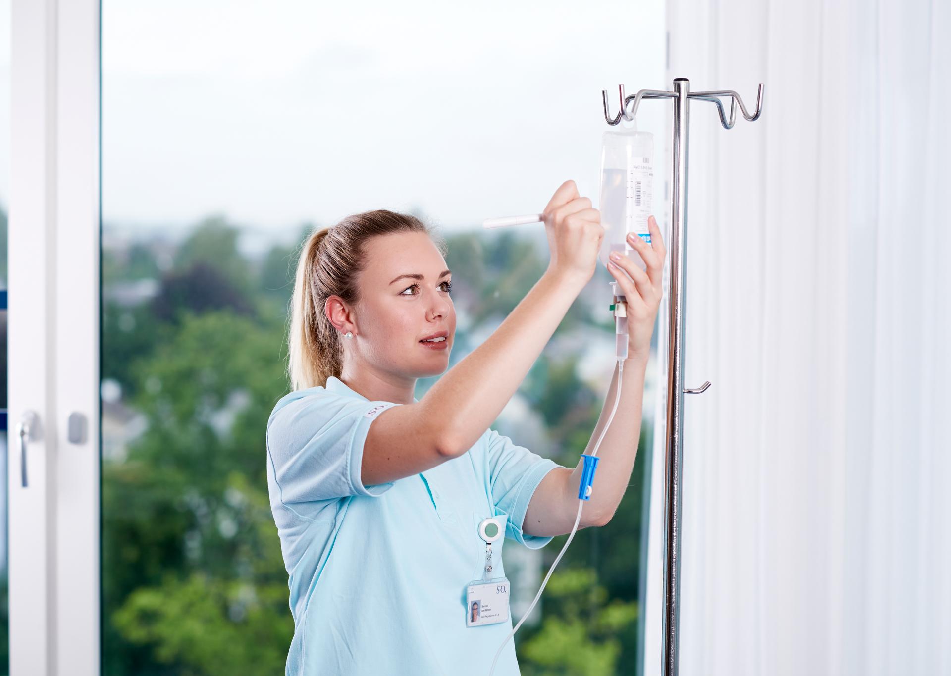 Pflegefachfrau befestigt Infusion