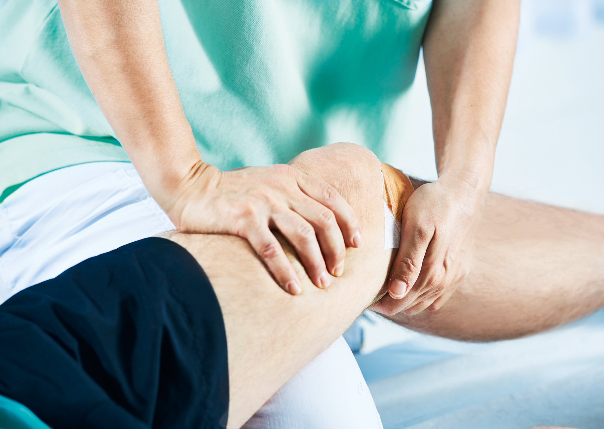 Physiotherapeutin behandelt Knie eines Patienten