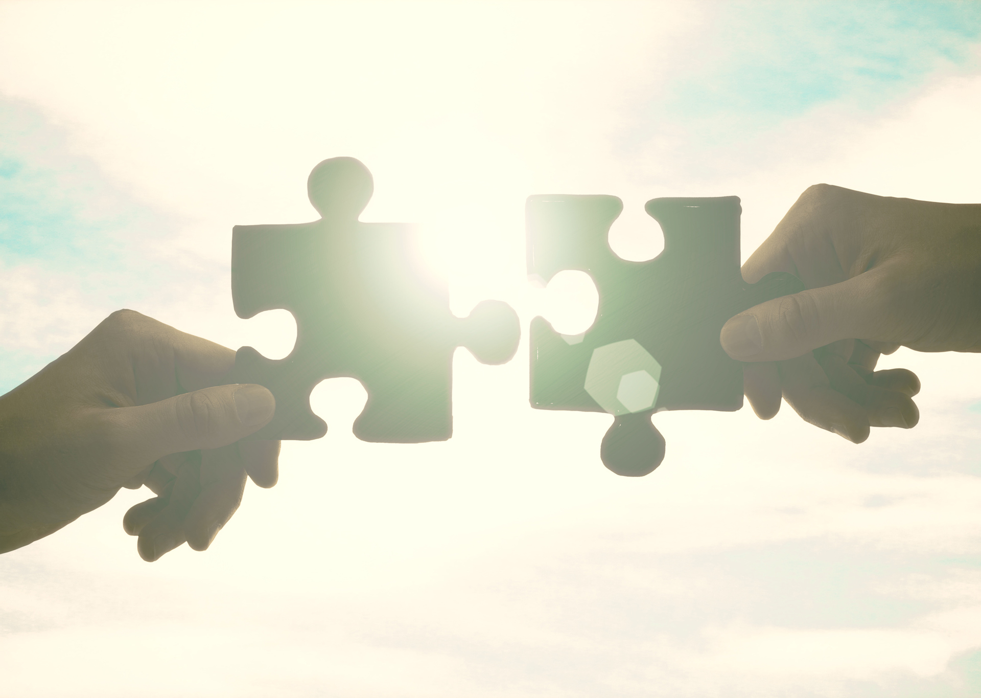 Zwei Hände halten zwei Puzzle-Teile aneinander