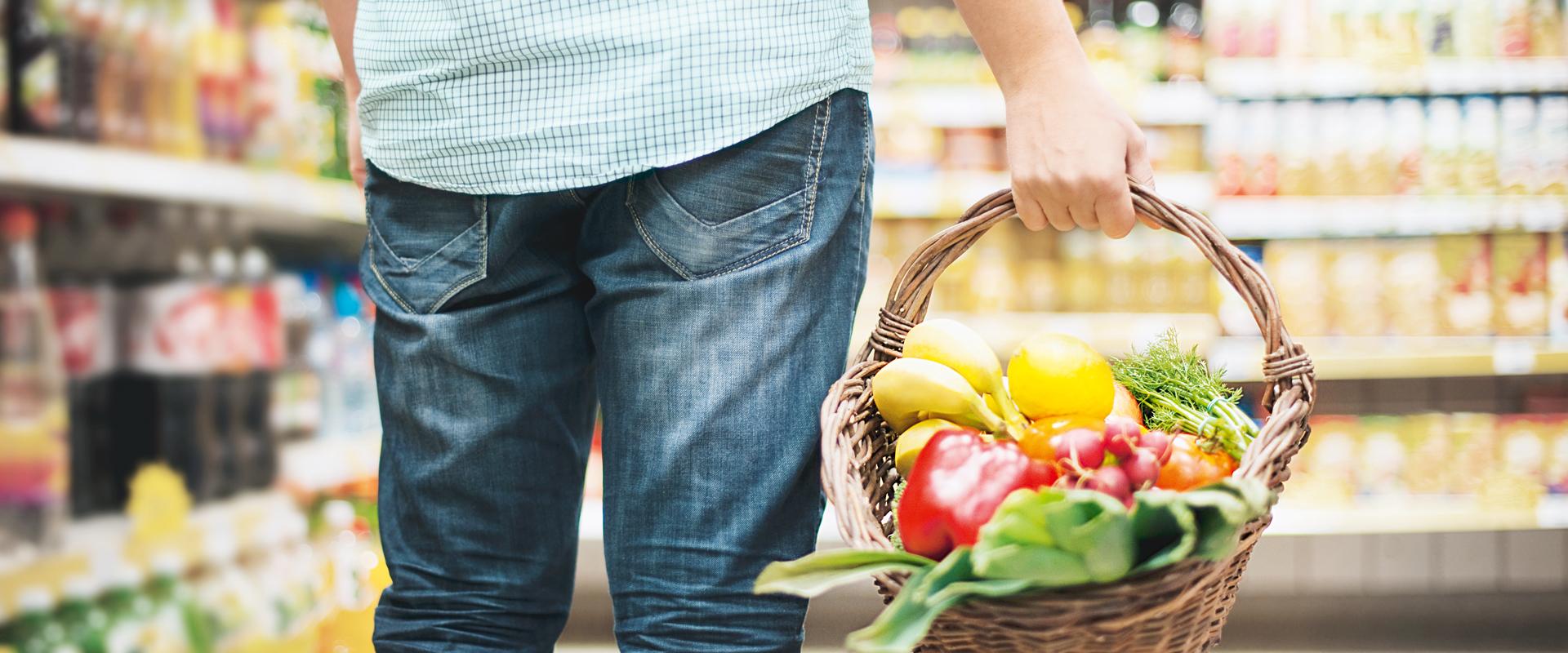 Mann trägt Korb mit frischem Gemüse und frischen Früchten